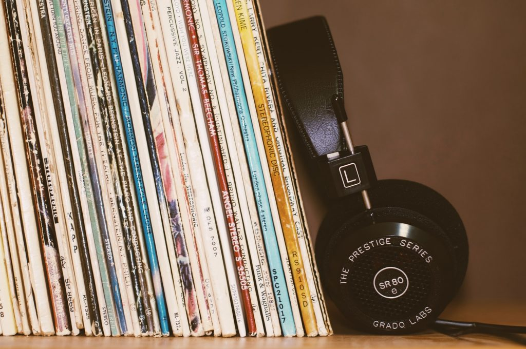 wireless headphones leaning on record collection